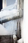 Icicles From The Roof Gutter And Down Pipe