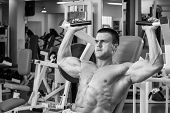 Постер, плакат: Man at the gym Man makes exercises dumbbells