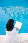 Attractive Lady Reading In The Swimming Pool