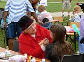 image of senior-citizen  - a senior citizen is face painting a young girl on a picnic - JPG