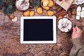 Tablet And Christmas Decor On Wooden Background poster
