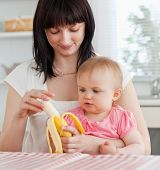 Charming brunette woman pealing a banana while holding her baby on her knees in the kitchen