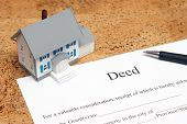 picture of deed  - A scale house on some forms for a deed to conceptualize on the financial investment - JPG