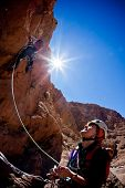 A female climber belays the leader during a rock climbing in Todra Valley, Atlas, Maroc, Africa.