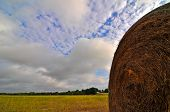 hay bale against vibrant blue,cloud filled sky