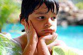 A Hispanic boy daydreams by the pool