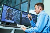 Security worker during monitoring. Video surveillance system. poster
