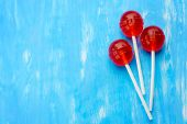 Three Ball Red Lollipops On White Sticks. Central Lollipop Above, At The Right Edge, On The Blue Bac poster