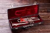 Trumpet With Mouthpiece In Velvet Box. Classical Trumpet With Red Bow In Case On Wooden Background.  poster