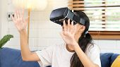 Young Asian Woman Exciting In Vr Headset Looking Up And Trying To Touch Objects In Virtual Reality A poster