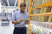 Young Man Shopping Or Working In A Hardware Warehouse Standing Checking Supplies On His Tablet. poster