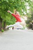 Feeling Really Energetic. Lively Small Girl Jumping With Energetic Moves. Active Kid Being In Energe poster