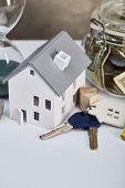 House Model On White Table With Keys And Moneybox, Real Estate Concept poster