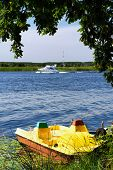 Yellow Catamaran With Pedals On The River Bank With A Modern Yacht poster