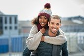 Portrait of young man giving piggyback ride to african woman. Happy boyfriend and smiling girlfriend poster