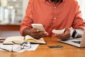 Closeup of african man hands using phone to calculate expenses. Man checking invoice balance on mobi poster
