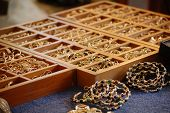 Gold rings and colorful beaded bracelets in wooden display box