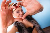Winter Sport Concept. Woman Wearing Ski Goggles At Head And Furry Waistcoat Making Heart Symbol With poster