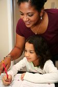 picture of school child  - Young girl at school with teacher looking over her shoulder - JPG