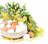 Basket with Easter eggs and spring flowers on white background