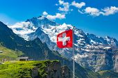 Swiss Flag Waving And Tourists Admire The Peaks Of Monch And Jungfrau Mountains On A Mannlichen View poster