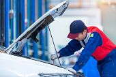 Young Man Car Mechanic In A Car Repair Service Center Is Analyzing Engine Problems And Checking The  poster