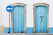 Two Blue Doors And Blue Traffic Sign