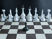 Lonely Black Pawn Standing Alone Against Whole Army Of White Figures On Chess Board. Concept Depict  poster
