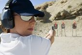 Young woman aiming with handgun at combat training