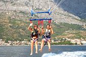 image of parasailing  - two young girls parasailing over adriatic watres in Croatia - JPG