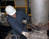 stock photo of pressure vessel  - An engineer working on a steam valve on top of a 60 - JPG