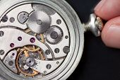 image of analog clock  - Close up of analog clock mechanics with finger winding it up - JPG