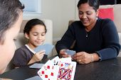 stock photo of playing card  - Family playing cards together around the table - JPG