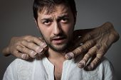 pic of choke  - Young bearded man choked by two huge hands on dark background - JPG