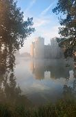 pic of slit  - Beautiful medieval castle and moat at sunrise with mist over moat and sunlight behind castle - JPG