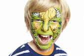 stock photo of goblin  - Young boy with face painting monster smiling on white background - JPG