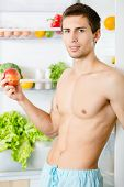 Man keeps apple standing near the opened refrigerator. Concept of healthy and dieting food