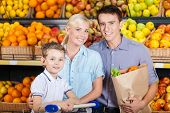 Happy family against shelves of fruits goes shopping. Father keeps a paper bag with fruits and son s