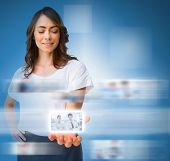Stylish businesswoman presenting picture of coworkers on digital interface on blue background