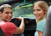 Cheerful couple looking at camera over shoulder while having a ride in cabriolet