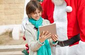 Midsection of Santa Claus and boy using digital tablet outdoors