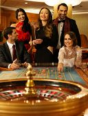 image of roulette table  - Group of young people behind roulette table in a casino - JPG