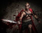 stock photo of blood  - Wounded gladiator attacking with sword covered in blood - JPG