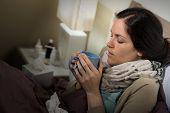 Ill Caucasian woman drink tea in bedroom suffering flu cold