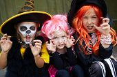 stock photo of cult  - Portrait of three Halloween girls looking at camera with frightening gesture - JPG