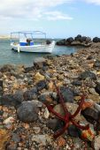 foto of safe haven  - A small Greek fishing boat or caique firmly anchored to a breakwater in southern Crete Greece - JPG