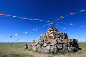 Praying Stone And Prayer Flags On Steppe