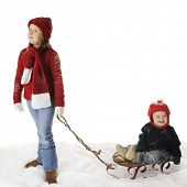 An elementary girl pulling her baby brother on a sled.  On a white background with plenty of space for your text over sled.