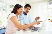 stock photo of card-making  - Indian Couple Making Online Purchase At Home - JPG