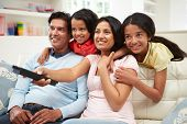 stock photo of sofa  - Indian Family Sitting On Sofa Watching TV Together - JPG